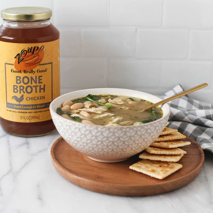 chicken soup with crackers and Zoup! chicken bone broth jar on kitchen counter platter